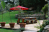Designer Clare MATTHEWS: THE STONE TERRACE with Green OAK TABLE AND BENCHES, Olive TREES IN TERRACOTTA CONTAINERS AND A Red Parasol