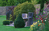 WOODEN SEATS AND TABLE On SLATE TERRACE with Box TOPIARY SHAPES AND Acer PALMATUM 'DISSECTUM' . Designer: JOHN MASSEY