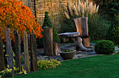 SLATE TERRACE Beside WILLOW FENCE with OAK CHAIRS AND TABLE, Acer PALMATUM 'DISSECTUM' AND Box TOPIARY SHAPES. Designer, JOHN MASSEY