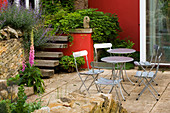 Metal CHAIRS SURROUND CIRCULAR TABLE IN Front of Red WALL On Patio (TERRACE). WINGWELL NURSERY, Rutland