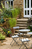 WINGWELL NURSERY, Rutland: VIEW of Patio with TABLE AND CHAIRS Infront of STEPS LEADING TO White DOORS