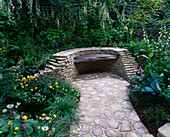 CHELSEA FLOWER Show 2005. Pause FOR THOUGHT COURTYARD Garden, DESIGNERS: LIZ ROBINSON AND PHIL KAYE: Dry STONE WALL with RECLAIMED TIMBER SEAT with SHADE-Loving PLANTS