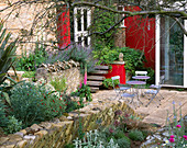 WINGWELL NURSERY, Rutland: VIEW TO THE BACK of THE HOUSE with Red WALL, STACHYS, PHORMIUM, Metal TABLE AND CHAIRS. Patio