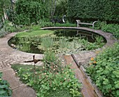 WINGWELL NURSERY, Rutland: RILL SPILLS INTO CIRCULAR Pool (POND) with STONE SEAT AND Water SCULPTURE 'New Moon' by GEORGE CUTTS