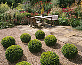 MAYROYD MILL HOUSE, Yorkshire: DESIGNERS: RICHARD EASTON AND Steve MACKAY - GRAVEL TERRACE with Box BALLS, WOODEN TABLE AND CHAIRS On Patio AND HERBACEOUS PERENNIAL BORDER