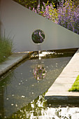 RICHARD JACKSONS GARDEN. DESIGNED by Clare MATTHEWS : Water Feature - RECTANGULAR POND / Pool with Metal SAIL AND WATERFALL. REFLECTION