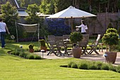RICHARD JACKSONS GARDEN. DESIGNED by Clare MATTHEWS - Patio, Box BALLS, TABLE AND CHAIRS, Parasol, CHILDREN PLAYING BADMINTON