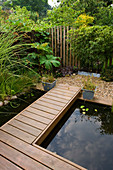 KATHY TAYLORS Garden, London: POND - POND with DECKED WALKWAY, SCULPTURE AND FENCE Made From WOODEN POSTS