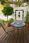 MEDITERRANEAN DECKED COURTYARD with STANDARD Bay, TILED Water Feature AND MOSAIC TABLE. SHADE CANOPY. DECKING, TRELLIS, VINE, KATHY Taylor'S Garden, London