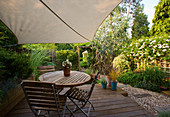 EXOTIC SHADE PLANTING of GRASSES, PHORMIUM, BAMBOO, Rosemary AND OTHER FOLIAGE PLANTS with CANOPY OVER DECKED Dining AREA IN SMALL Town GRAVEL Garden by KATHY Taylor, LONDON.