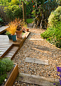KATHY TAYLORS Garden, London: BACK Garden VIEW Along GRAVEL PATH with SLEEPERS. DECKING with THREE CONTAINERS AND POND / Pool