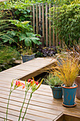 KATHY TAYLORS Garden, London: DECKED TERRACE AND WALKWAY Beside POND with CONTAINERS AND AFRICAN SCULPTURE with FENCE Made From WOODEN POSTS