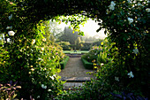 MARINERS Garden, BERKSHIRE. Designer FENJA ANDERSON - VIEW INTO THE ROSE Garden THROUGH an ARCH (Moon GATE) of ROSE 'City of York' TO THE Water LILY Pool with HERON SCULPTURE.