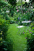 Amelia HEATH Garden, 1, CROSS VILLAS, SHROPSHIRE: THE SECRET Garden with LAWN, WOODEN TABLE AND CHAIRS