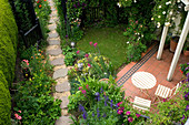 Amelia HEATH Garden: 1 CROSS VILLAS,SHROPSHIRE: Patio: TABLE AND CHAIRS. WOODEN with ROSE GOLDFINCH, GLADIOLUS BYZANTINUS, GRAVEL PATH, CLEMATIS ETOILE VIOLETTE, ACONITUM