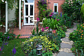 Amelia HEATH Garden, 1, CROSS VILLAS, SHROPSHIRE: Patio Beside THE HOUSE - WOODEN TABLE AND CHAIRS, Pergola, LANTERN, GLADIOLUS COMMUNIS BYZANTINUS, ACONITUM, PATH