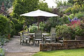 MARINERS Garden, BERKSHIRE. Designer FENJA ANDERSON - Patio with Wine AND Red BORDER AND UPPER Bank - A PLACE TO SIT - TABLE AND CHAIRS AND CANOPY - PHYGELIUS, PENSTEMON 'FIREBIRD