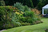 MARINERS Garden, BERKSHIRE. Designer FENJA ANDERSON -LAWN with CONSERVATORY AND HERBACEOUS BORDER with STIPA GIGANTEA, PHORMIUM TENAX, Cynara CARDUNCULUS, THALICTRUM FLAVUM