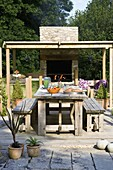 Designer Clare MATTHEWS: Devon GARDEN. OUTDOOR SEATING AREA. Patio with WOODEN TABLE AND BENCHES, COVERED Pergola AND OUTDOOR OVEN / KITCHEN AREA