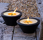 Designer Clare MATTHEWS: Devon GARDEN. LIGHTING: TWO LARGE CANDLES IN WOODEN CONTAINERS On THE Patio