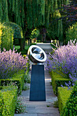 DAVID HARBER SUNDIALS: CHALICE SUNDIAL On PATH IN Formal Garden with Box HEDGING, LAVENDER On LEFT AND PEROVSKIA On RIGHT