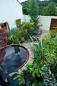 DARREN CLEMENT'S Garden, Staffordshire: COURTYARD Garden with MIXTURE of ARCHITECTURAL Evergreen SHRUBS. Black TABLE AND CHAIRS AND Hot TUB