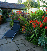 DARREN CLEMENT'S Garden, Staffordshire: COURTYARD Garden with Black Sun LOUNGER Beside BORDER with CROCOSMIA LUCIFER AND COTINUS Grace