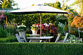 WILKINS PLECK, Staffordshire: Patio at BACK of THE HOUSE: A PLACE TO SIT - WOODEN TABLE AND CHAIRS with Parasol