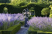 DAVID HARBER SUNDIALS: STAINLESS STEEL ARMILLARY SPHERE SUNDIAL IN Formal Garden SURROUNDED by Box HEDGES AND LAVENDER. EVENING Light