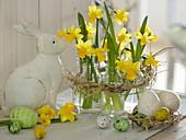 Narcissus 'Tete a Tete' (Narzissen), kleine Flaschen als Vasen im Strohkranz