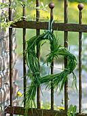 Kleines Herz aus Gras an rostigen Zaun gehängt