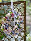 Kranz aus Frühlingsblüten an Zaunelement