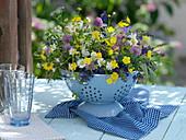 Wiesenblumen-Strauß in Schale im emaillierten Sieb