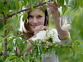 Weißer Kräuterstrauß im Glas und kleine Windlichter an Baum gehängt : 1/2