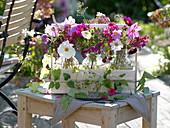 Flaschen mit Sommerblumen in Flaschenträger