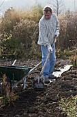 Mann bringt Kompost im Garten aus