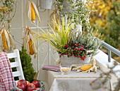 Herbstbalkon mit bepflanzter Jardiniere aus Metall