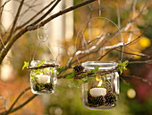 Einmachgläser als Windlichter mit Drahtbügel an Baum gehängt