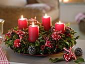 Adventskranz aus Ilex (Stechpalme) dekoriert mit roten Herzen und Zapfen