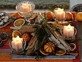 Ungewöhnlicher Adventskranz mit Sternkerzen in Gläsern auf Holztablett