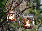 Kleine Gläser als Windlichter an Baum gehängt