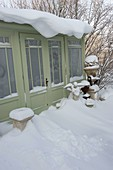 Verschneites Gartenhaus mit Engel, Amphoren und Podesten als Deko