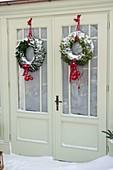 Verschneites Gartenhaus weihnachtlich dekoriert mit Kränzen,
