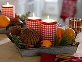 Zinktablett mit rot-weiß-karierten Kerzen, Pomander, Orangen