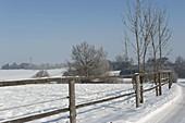 Blick über verschneite Koppel in die Landschaft