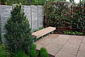 Sichtschutzwand aus Granitstelen, Terrasse und Bank aus Naturstein, Spalier aus Photinia villosa (Glanzmispel), Pinus (Kiefer)