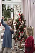 Mädchen mit stilisiertem Weihnachtsbaum als Adventskalender