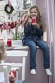 Mädchen mit Adventskalender am Fenster