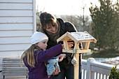 Mutter und Tochter befüllen ein Vogelfutterhaus