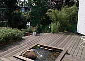 Holzterrasse mit integrierten Teich